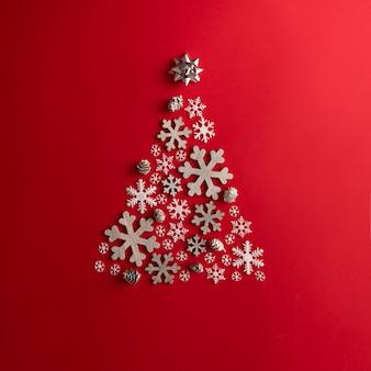 Świąteczna i noworoczna czerwona ściana z choinką z płatków śniegu. koncepcja wakacje. leżał na płasko.