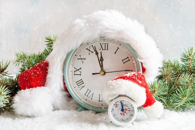 Świąteczna i noworoczna kompozycja z dużymi i małymi zegarami w czapce mikołaja, które pokazują wigilię wakacji