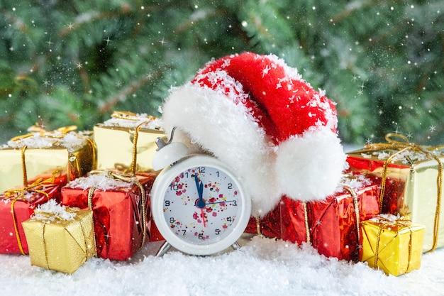 Świąteczna i noworoczna kompozycja z zegarem w czapce mikołaja przedstawiająca wigilię świąt, gałęzie jodły, dekoracje świąteczne i prezenty na śniegu