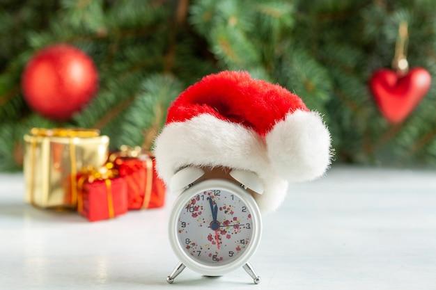 Świąteczna i noworoczna kompozycja z zegarem w czapce mikołaja przedstawiająca wigilię święta, gałęzie jodły, dekoracje świąteczne i prezenty