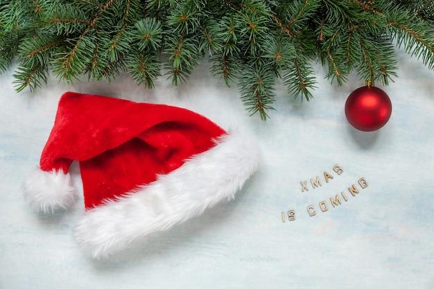 Świąteczna i noworoczna kompozycja z zegarem w santa hat pokazujący wigilię wakacji. widok z góry, z bliska na jasnoniebieskim tle.