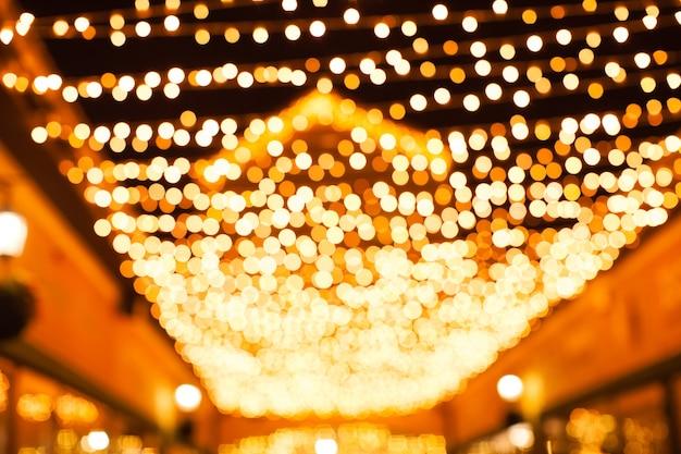 Świąteczna iluminacja w mieście. rozmyte złote światła, piękny bokeh między budynkami