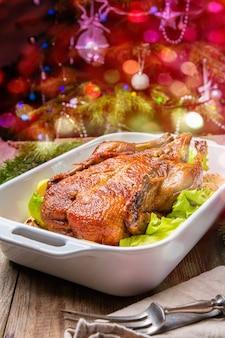 Świąteczna kaczka z jabłkami i ziołami na białej patelni z dekoracjami świątecznymi