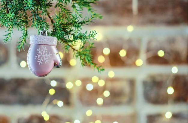 Świąteczna kartka bożonarodzeniowa z gałązką choinki z zabawką na murze