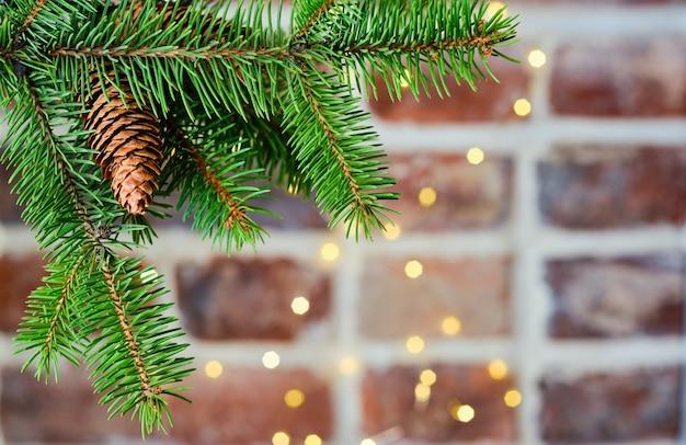 Świąteczna kartka świąteczna z gałązką choinki na stole ceglany mur ozdobiony girlandą, selektywne focus.