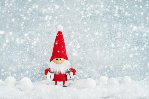 Świąteczna kartka z pozdrowieniami. santa gnomu tło z choinką i śniegiem.