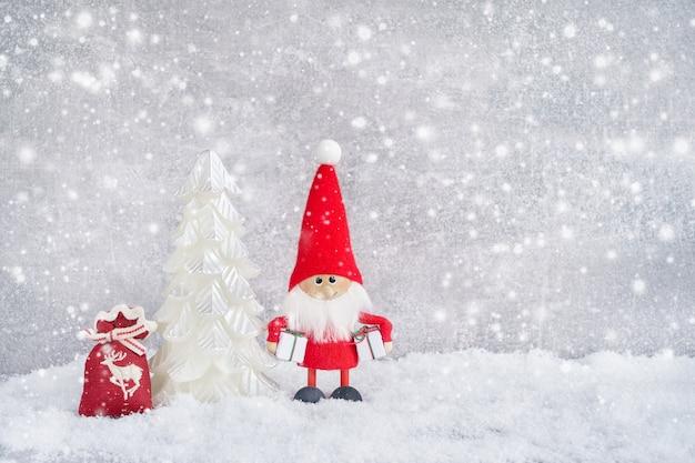 Świąteczna kartka z pozdrowieniami. święty mikołaj tło z choinką i śniegiem. copyspace