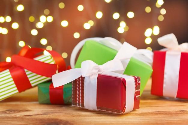 Świąteczna kartka z życzeniami z pudełkami prezentowymi na tle rozmytego światła