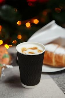 Świąteczna kawa i rogaliki z prezentami i zabawkami na tle choinki.