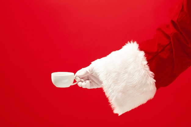 Świąteczna kawa. santa ręka trzyma filiżankę kawy na białym tle na czerwonym tle z miejscem na tekst.