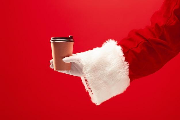 Świąteczna kawa. santa ręka trzyma filiżankę kawy odizolowane na czerwono