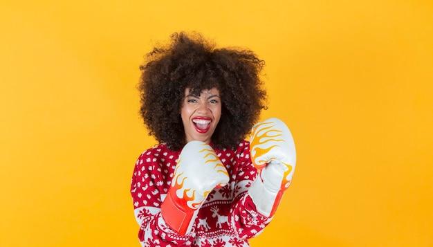 Świąteczna kobieta arfo, świąteczny sweter i rękawice bokserskie, żółte tło