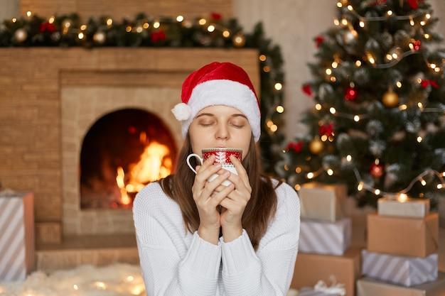 Świąteczna kobieta pije gorącą herbatę lub kawę, cieszy się napojem z zamkniętymi oczami, trzymając kubek w obu rękach, siedzi w salonie ze świątecznymi dekoracjami, dziewczyna w ciepłym swetrze i czapce mikołaja.