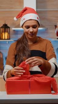 Świąteczna kobieta przygotowująca prezenty z papierem do pakowania