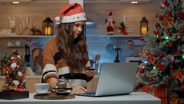 Świąteczna kobieta trzymająca kartę kredytową, aby robić zakupy online