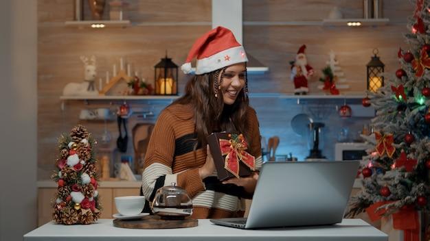 Świąteczna kobieta za pomocą laptopa do rozmowy wideo w wigilię bożego narodzenia
