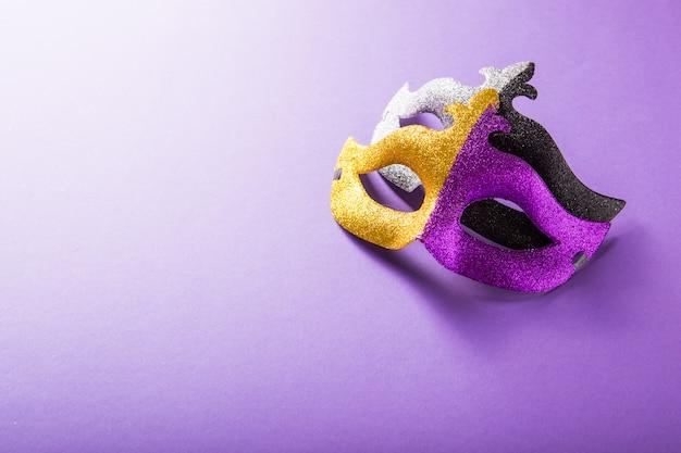 Świąteczna, kolorowa grupa mardi gras lub karnawałowej maski na fioletowym tle. maski weneckie.