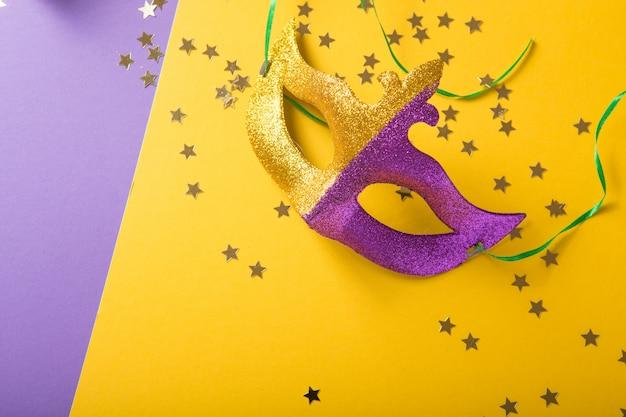 Świąteczna, kolorowa grupa mardi gras lub maski karnawałowe na żółtym fioletowym tle. maski weneckie.