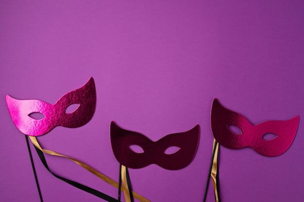 Świąteczna, kolorowa mardi gras lub maska karnawałowa i akcesoria na fioletowej ścianie. leżał na płasko, widok z góry, miejsce na kopię