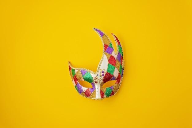 Świąteczna, kolorowa mardi gras lub maska karnawałowa i akcesoria na żółtej ścianie. leżał na płasko, widok z góry, miejsce na kopię