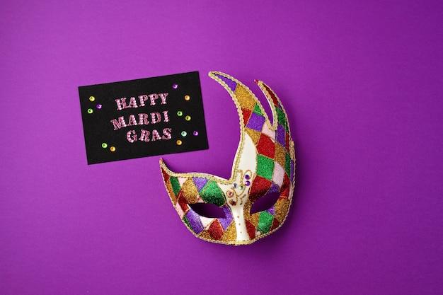 Świąteczna, kolorowa maska mardi gras lub karnawałowa i kartka z życzeniami na fioletowej ścianie. leżał na płasko, widok z góry, miejsce na kopię
