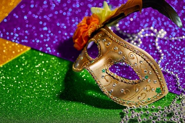 Świąteczna, kolorowa maska mardi gras lub karnawałowa oraz koraliki na złotym tle. maski weneckie. koncepcja obchodów karnawału weneckiego.