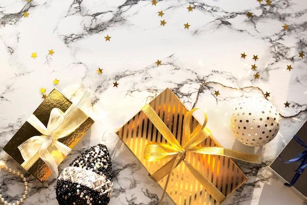 Świąteczna kompozycja - bombka bożonarodzeniowa, kulki, płatki śniegu, zabawki na marmurowym tle