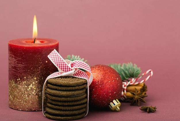 Świąteczna kompozycja, boże narodzenie, bordowa świeca z ogniem, stos czekoladowych ciasteczek, drzewo, biała wstążka z czerwonym wzorem, czerwona błyszcząca bombka, laski cynamonu, anyż, bordowe tło,