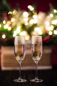 Świąteczna kompozycja choinki ozdobione złotymi światełkami, girlandami, zabawkami i pustymi kieliszkami do szampana.