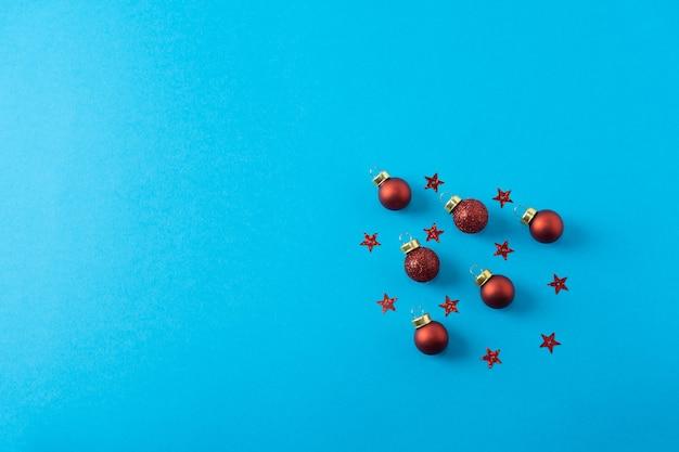 Świąteczna kompozycja czerwone bombki i wzory gwiazd na niebieskim tle banner