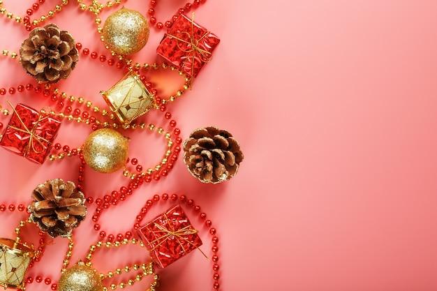 Świąteczna kompozycja dekoracji i zabawek świątecznych na różowym tle. wolne miejsce na tekst.