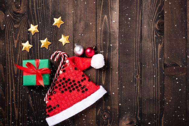 Świąteczna kompozycja dekoracyjna prezentująca czapkę mikołaja, gwiazdę, ornament i ozdoby świąteczne