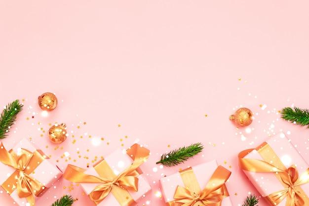 Świąteczna kompozycja dekoracyjna z papierowym pudełkiem, złotymi bombkami i kokardą ze złotej wstążki na różowym tle.