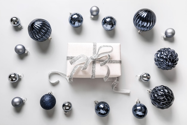 Świąteczna kompozycja klasycznych niebieskich kulek i pudełka na szaro. widok z góry. boże narodzenie. karta z pozdrowieniami świątecznymi