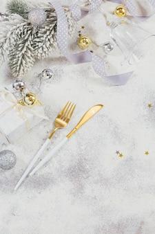 Świąteczna kompozycja kreatywna ze sztućcami, prezent na boże narodzenie, gałęzie jodły, dekoracja. zimowe wakacje tło. granica, płaskorzeźba, widok z góry, miejsce na kopię.