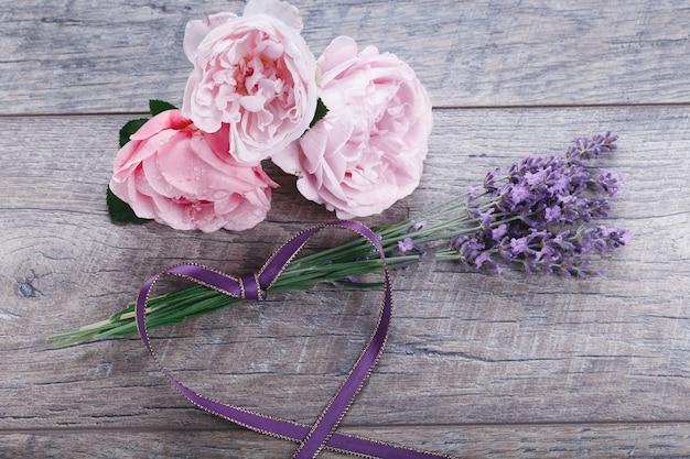 Świąteczna kompozycja kwiatów angielskich róż z lawendą wstążkową na drewnianym tle