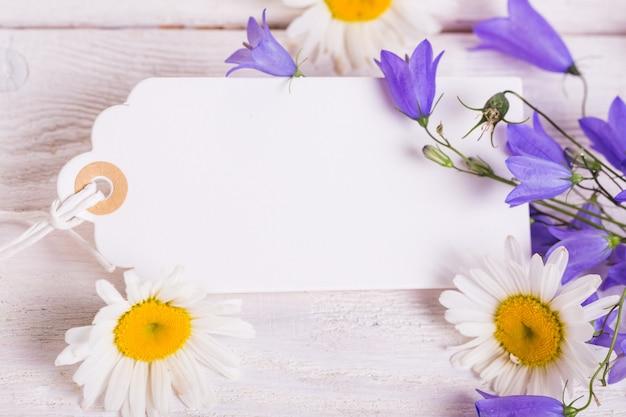 Świąteczna kompozycja kwiatów. obszar roboczy z polne kwiaty stokrotki, dzwony kwiaty, kartkę z życzeniami na białym tle. widok z góry, układ płaski. koncepcja urodzin, matki, walentynek, kobiet, ślubu