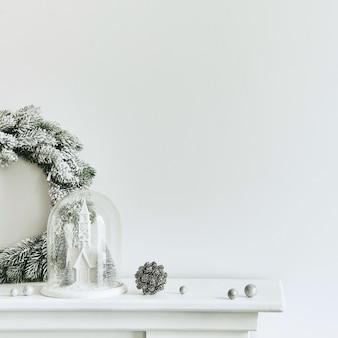 Świąteczna kompozycja na białym kominie we wnętrzu salonu z piękną dekoracją. choinka i wieniec, świece, gwiazdy, światło. skopiuj miejsce. szablon.