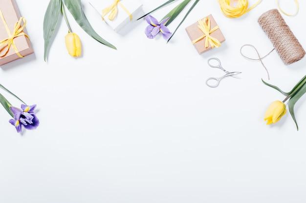 Świąteczna kompozycja na białym stole: fioletowe i żółte kwiaty, pudełka z prezentami, wstążki