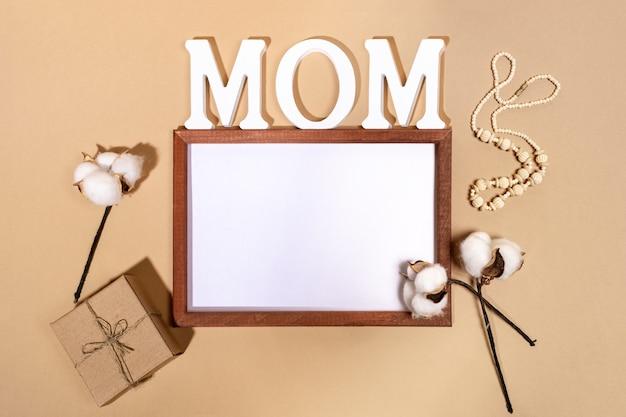 Świąteczna kompozycja na dzień matki z ramką, białymi literami mom, pudełkiem prezentowym diy i bawełnianymi kolbami