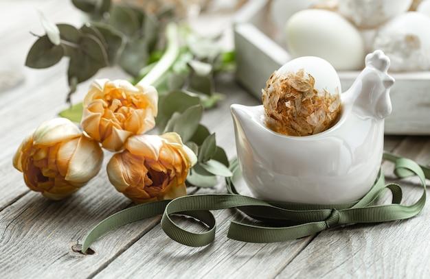 Świąteczna kompozycja na wielkanoc z ozdobnymi jajkami i świeżymi kwiatami.