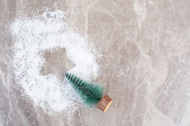 Świąteczna kompozycja nadruku gwiazdy w kupie pudru waniliowego i figurka drzewa na marmurze.