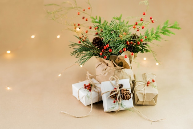 Świąteczna kompozycja naturalnych materiałów. zapakowany prezent świąteczny, koc z dzianiny, szyszki, gałęzie jodły. leżał płasko, widok z góry