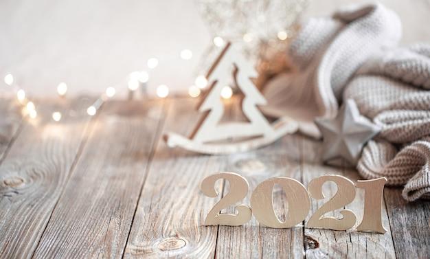 Świąteczna kompozycja noworoczna z drewnianym numerem nowego roku na jasnym tle niewyraźne z dekoracją świąteczną.