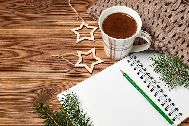 Świąteczna kompozycja otwartego pustego notatnika, filiżanki kawy, szalika i gałęzi jodły na drewnianym tle