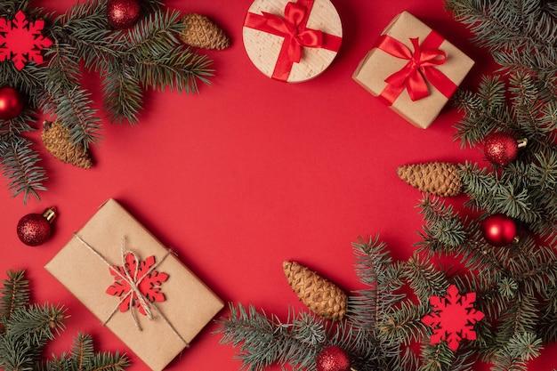 Świąteczna kompozycja płaska z sosną, pudełkami na prezenty i wystrojem świątecznym na czerwonym tle, miejsce na kopię. układ noworoczny i świąteczny