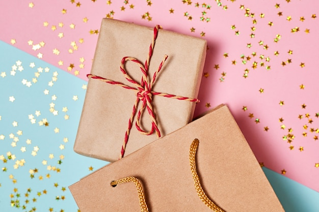 Świąteczna kompozycja pudełek prezentowych w papierowej torbie na drewnianym tle z cekinami