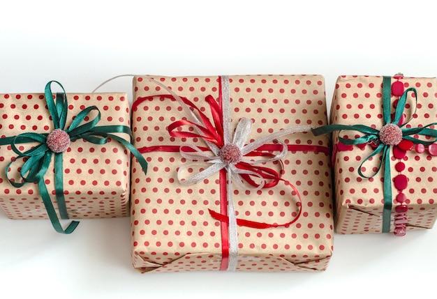 Świąteczna kompozycja różnych pudełek na prezenty zawiniętych w papier rzemieślniczy i ozdobionych satynowymi czerwonymi i zielonymi wstążkami.