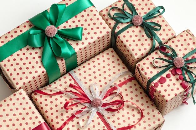Świąteczna kompozycja różnych pudełek na prezenty zawiniętych w papier rzemieślniczy i ozdobionych satynowymi wstążkami. widok z góry, płaski układ.