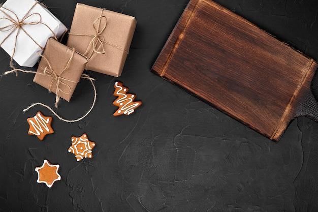 Świąteczna kompozycja świąteczna ciasteczka prezenty świąteczna dekoracja na czarnym tle płaska leżanka widok z...